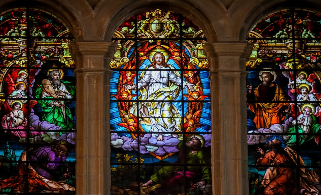 MALAGA, SPAIN - NOV 29, 2013: Stained glass window depicting Jesus, Moses and Saint Paul, in the cathedral of Malaga, Spain.